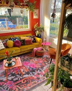 Beautiful boho living room design with floral motifs in red small square tables yellow sofas brown sofas colorful sofa cushions rattan baskets and green plants as a complement