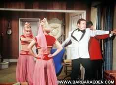 """This fun shot comes from the set of """"I Dream of Jeannie"""" fourth season episode """"Jeannie Go Round."""" Here we see Jeannie and her wicked twin sister Jeannie (posing as Jeannie) in a battle. Major Healey is trying desperately to keep Dr. Bellows from seeing what is happening while Maj. Nelson does the same with Mrs. Bellows in the dining room."""