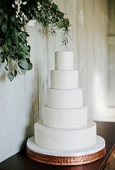 A five-tier white wedding cake with a pressed floral design by @Twistedfigcake | Brides.com