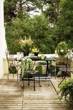 Garden patio with wood deck and iron bistro chairs.