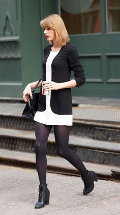 Taylor Swift wears a white dress and a black relaxed jacket with tights and black booties.
