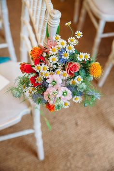 Wild flower chair décor. Bright colourful wedding flowers. For more inspiration visit www.weddingsite.co.uk