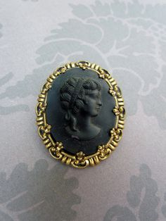 Vintage cameo brooch in black and gold .