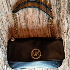 NWT: Michael Kors Fulton black w/ gold leather bag NWT... Authentic Michael Kors Fulton small shoulder flap bag. Black leather with gold chains and hardware. Perfect condition, ..new with tags! Gorgeous!   Width 4.1 in, Height 2.4 in, Depth 0.8 in..........make me an offer Michael Kors Bags Shoulder Bags