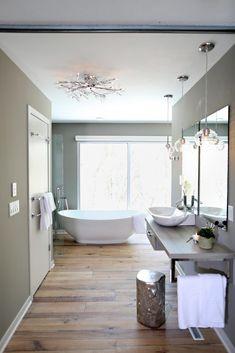 A modern gray bathroom with floor to ceiling windows, hardwood floors and single vanity, as seen on HGTV's Bath Crashers.