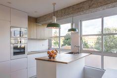 Cocina lacada blanca combinado con frentes de roble con isla central en alistonado de roble. Lámparas vintage en tonos verdes