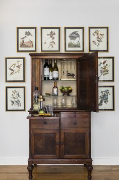 TRIM DESIGN CO. | This vintage dental cabinet was recreated to become a unique home bar in our kitchen renovation project. The beautiful natural wood adds personality and warmth to the new kitchen. A collection of vintage Audubon prints flanks the antique bar cabinet. Convenient wood trays slide out for mixing cocktails and the cabinet is lit from within.   #trimdesignco #homebarideas #wetbar #homebar #vintagebarideas