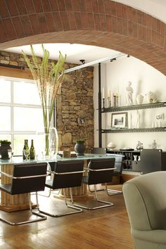 Exposed architectural materials—brick arch and stone wall; column bases w/ glass top table; Jeff Herr photo