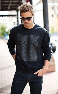 Shop this look on Lookastic:  http://lookastic.com/men/looks/black-sunglasses-black-print-crew-neck-sweater-navy-jeans/8512  — Black Sunglasses  — Black Print Crew-neck Sweater  — Navy Jeans