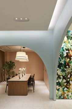 the interior of maison lexia in osaka features arched walls in pastel hues and a display of plant extracts that links to the brand\'s in-house production processes.