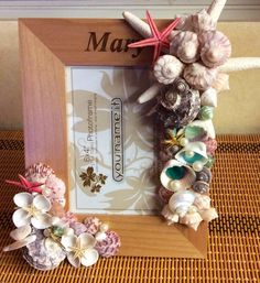 A wooden picture frame, personalized, by carving a name on it, decorated by natural sea shells and golden details. It is made, based on the abilities we have on the right and the left side of our brain.