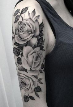 A grayscale rose tattoo designed on the shoulder. Consisting of three roses colored and shaded with black ink against the skin to depict solidity. The leaves and stems all around the roses are all inked different shades of black. #tattoofriday #tattoos #tattooart #tattoodesign #tattooidea