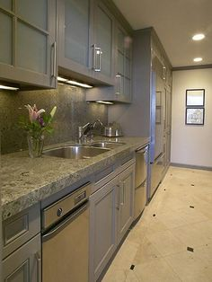 Contemporary hardware in a brushed-nickel finish blends seamlessly with the gray-colored cabinets and counter, as well as the stainless steel appliances, for a soothing, unified look in this galley kitchen.