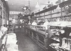GROCERY INTERIOR, 1912. Henry Lindemann's grocery and delicatessen at the southwest corner of 68th Avenue (originally Hughes Street) and Fresh Pond Road. Note the fresh flowers hanging from the ceiling; a large block of ice cools the delicatessen showcase. The store featured Adolf Gobel's meats. A coffee-grinding mill is at left. Fresh Pond Road is still a lively shopping center. (Robert F. Eisen collection.)