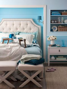 Tucked In - Convenient built-ins made arranging this bedroom a snap. The stylish tufted headboard tucks snugly into a small alcove set off as the room's focal point with crisp white trim and cheery blue beaded-board panels. Nearby, shelving offers storage and display space for chic flea market accessories and books...
