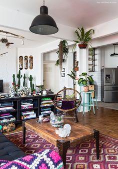 sala de estar de um apartamento descolado, com sofá de couro preto, tapete rosa e muitas plantas penduradas