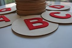"""great idea - use felt sticky back letters on 3"""" wooded circle discs (wooden art isle at Michaels or JoAnn's) to make tactile letters"""