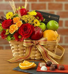 Charming basket filled with orchard-fresh apples, oranges and sweet chocolates (a perfect mix for sharing) along with a vibrant arrangement of red and orange #roses, yellow daisies and more. #giftbaskets