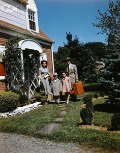 1940s 1950s Family Father Mother Daughter Son Leaving Suburban House Carrying Luggage
