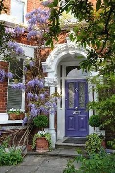 Two-step entrance with a periwinkle-colored door, embraced by ornate white trim and a wisteria... sublime.