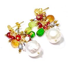 Ivory freshwater pearls, 13 mm, dangle beneath clusters of red burgundy and silver grey small peacock pearls mixed with red opal and pyrite rondelles and gemstone briolettes of chrome diopside, peridot and hessonite garnet to create these colorful dangle earrings. Tiny ivory pearls drape down over the lustrous ivory pearls. Tiny small gold hematine rondelles are added to the gold vermeil ball headpins for a bit a subtle gold sparkle. Perfect gift for someone special or to wear year round…