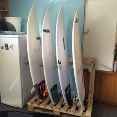 A DIY pallet surfboard rack storing 4 white surfboards vertically in a kitchen next to a fridge