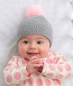 Newborn Cozy Cap Free Knitting Pattern in Red Heart Yarns -- Use this quality yarn that has been tested for harmful substances to knit the perfect baby hat. Body of hat is Garter Stitch with a Seed Stitch edging, and a contrast pom pom tops it off in style!