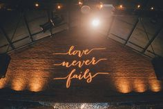 "Modern wedding reception idea - quote wedding reception decor - ""love never fails"" projected on wall {OLLI STUDIO}"