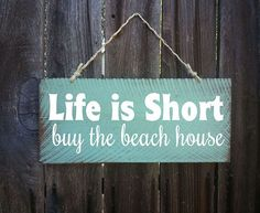 Life is Short Buy The Beach House sign. Measures 17 wide x 7 1/2 tall. Hand painted on 1/2 cedar with a distressed beach look.
