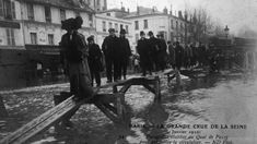 The 1910 flood in Paris lasted for two months.People balancing their way along a precarious-looking set of planks raised above the water.