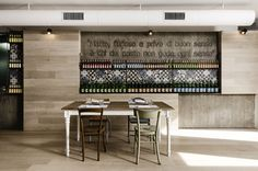 Turning the floor finish up the walls for a monolithic look - KOOK Osteria & Pizzeria by Noses Architects In Rome, Italy