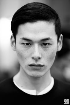 He has a very skinny face, you can easily see the bone structure on his face. His cheeks are very prominent. He also has typical asian single eyelid, and he has a large and wide lip.