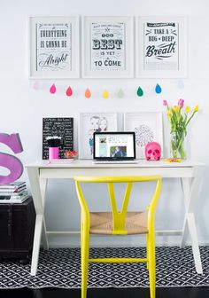 Sweet girl's desk featuring black and white art prints over white x-base desk paired with bright yellow Hans Wegner Wishbone Chair over black and white diamonds rug.