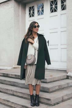 White sweater+golden pleated midi skirt+black ankle boots+dark green coat+blush crossbody bag+sunglasses. Fall Casual Outfit 2017