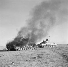 A British Crusader tank passes a burning German Pzkw Mk IV tank during Operation Crusader.