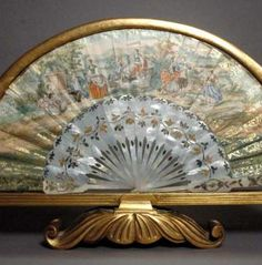 Antique Continental hand painted mother of pearl fan encased in a beautiful frame. We believe this fan is 18th or early 19th. Skillfully hand painted gauche pastoral scene depicting courting couples with a mountainous landscape background and raised gilded motifs. Frame is a gilt wood fan-shaped and scrolled footed frame century.