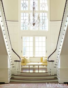 A yellow striped bench beckons between mirrored stairwells.<br /><br /><em><strong>Bench, Circa Interiors & Antiques, in Fabricut and Schumacher silk taffetas. Pillows in Harlequin fabric. Chandelier, Paul Ferrante.<em> Image originally appeared in the March/April 2012 issue of VERANDA.</em></strong><br /></em><br /><br />INTERIOR DESIGN BY <strong>JANE SCHWAB</strong>