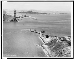 Construction of the Golden Gate Bridge, ca. A trestle reaches out from the San Francisco shore to the foundation of the north tower. Famous Buildings, Famous Landmarks, Bridge Construction, Under Construction, San Francisco California, San Francisco Bay, Old Pictures, Old Photos, Antique Photos