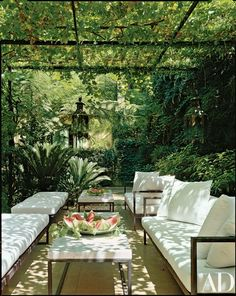 """""""The garden and sitting area are separated from the house by layers of different types of trees organically scattered,"""" says Richani. """"It's shaded by vines and lined with gardenias."""" The benches, tables and sofas are the architect's design 