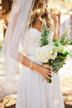 The floral elements of this wedding dress easily complement a simple bouquet. #MarriedInLV