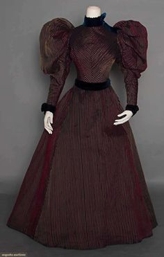 "STRIPED COTTON DAY DRESS, c. 1895 Go Back Lot: 83 November 12, 2014 New York City 2 piece, black self stripe cotton w/ raised yellow & red pinstripes, huge leg 'o mutton sleeves, black velvet trim, A line skirt, B 30"", W 21"", Skirt L 39"", (waistband replaced, skirt's back gathers messy, velvet collar band replaced w/ dark blue velvet, few small pulls in fabric) very good. Suddon-Cleaver Costume Collection"