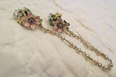 This retro Sweater clip is very pretty. Im estimating it is from somewhere between the 1950s - 1960s. The ends each have 3 painted pastel flowers