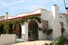 Spanish Mission house  wrought iron, low pitched roof, arcaded porch with adjoining arches