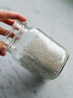 Roll jar around to allow glitter to coat all of the areas where glue was applied. Pour excess glitter back into the container to be reused.
