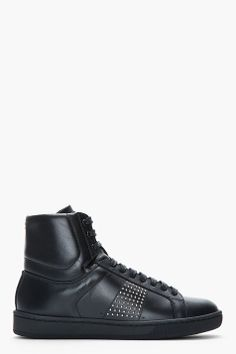 Saint Laurent Black Studded Leather Classic High_top Sneakers -  Saint Laurent Black Studded Leather Classic High_top Sneakers Saint Laurent High top leather sneakers in black. Round toe. Black ace up closure with black eyelets. Logo print at tongue in gold. Padded collar and tongue. PAneled upper. Embossed logo at heel collar and outer side. Mini faceted...