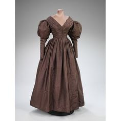 Romantic Period: this dress took place in the romantic period in the early 19th century. It is color a auburn brown matching natures surroundings and has a lower cut neckline and puffed up sleeves on the biceps/ low shoulders. Made of silk.