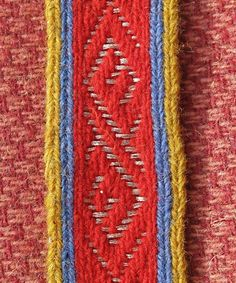 Replica Viking metal brocade. The metal threads survive in graves still folded into the original weaving pattern so the braids can be accurately reconstructed. Tablet woven in Shetland wool and sil...