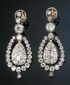A Pair of Antique Diamond Ear Pendants  Each comprising an old-cut diamond-set pear-shaped drop suspended within an independent diamond frame to the old-cut diamond collet line surmount, circa 1850, mounted in silver and gold