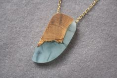This pendant has been handmade from Australian Olive wood and a mixture of pale blue and white resin. The pendant looks best on a darker shirt which makes