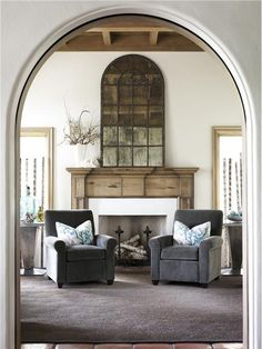 Arch doorway + wooden mantle + chevron fireplace + antique mirror.